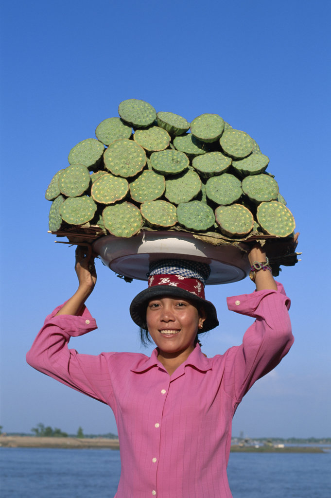 Portrait of a young woman carrying local produce on her head, Phnom Penh, Cambodia : Stock Photo