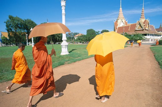 Rear view of three monks walking with umbrellas, Phnom Penh, Cambodia : Stock Photo