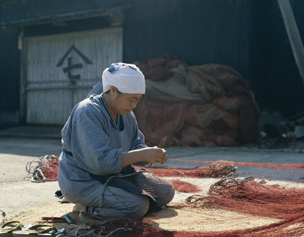 Mid adult woman repairing a fishing net, Honshu, Japan : Stock Photo