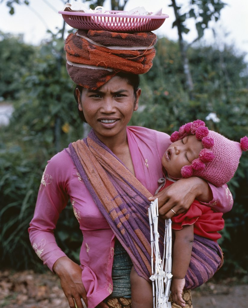 Stock Photo: 442-7034 Portrait of a mid adult woman holding her baby, Kintamani Market, Bali, Indonesia