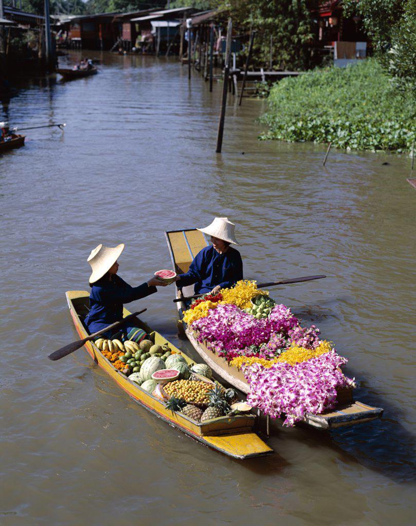 Two female vendors in boats selling fruit and flowers, Floating Market, Damnoen Saduak, Bangkok, Thailand : Stock Photo