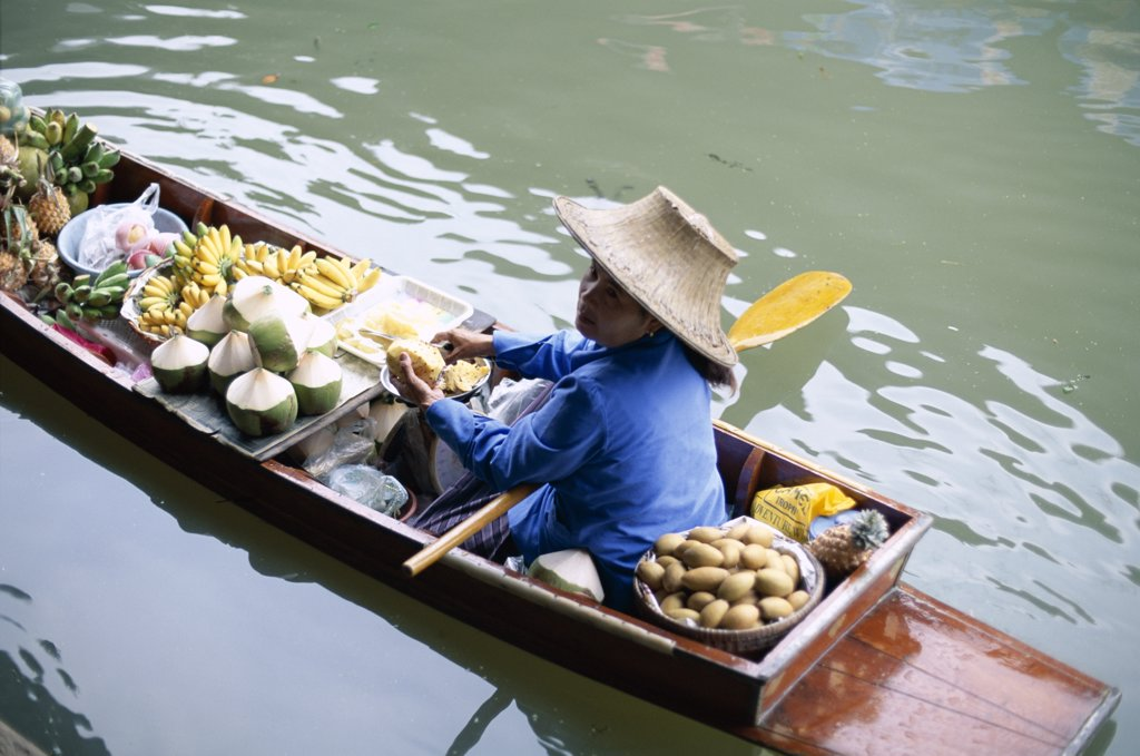 Female vendor in a boat selling fruit, Floating Market, Damnoen Saduak, Bangkok, Thailand : Stock Photo