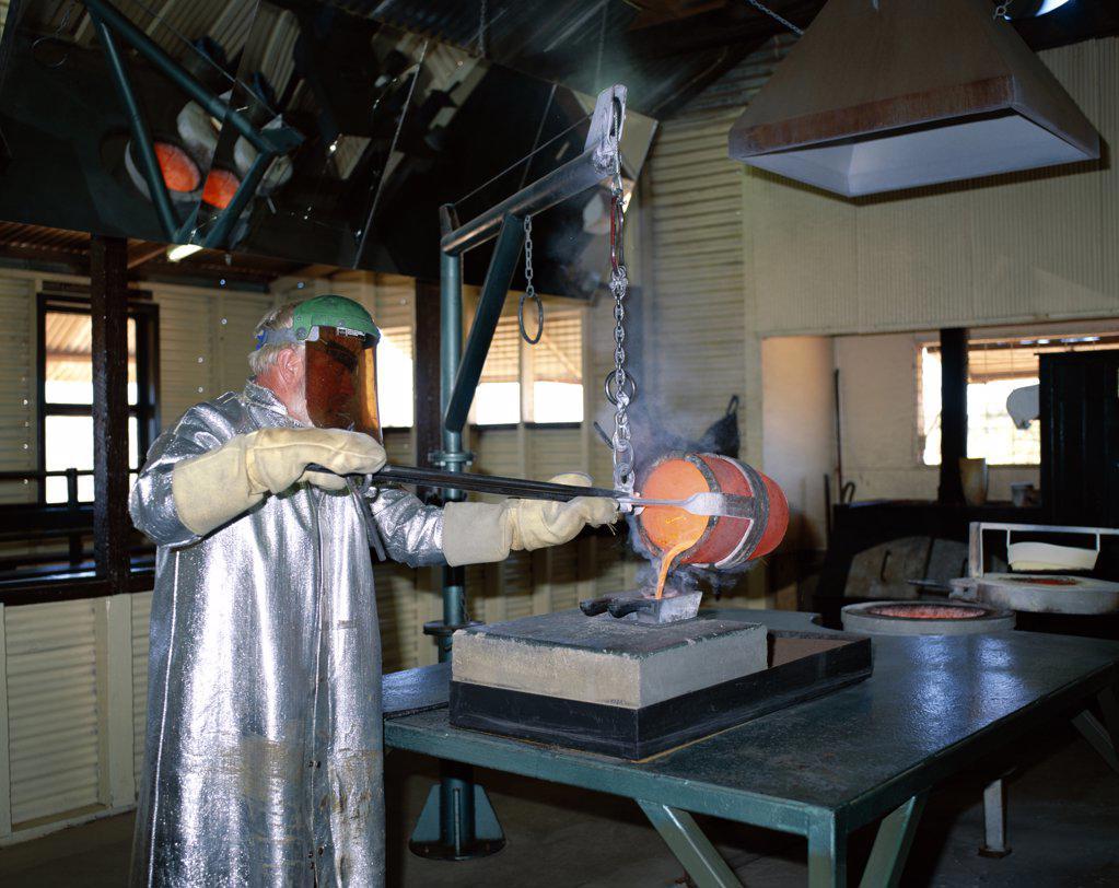 Person in protective clothing pouring molten metal, Hannas North Tourist Mine, Kalgoorlie, Western Australia, Australia : Stock Photo