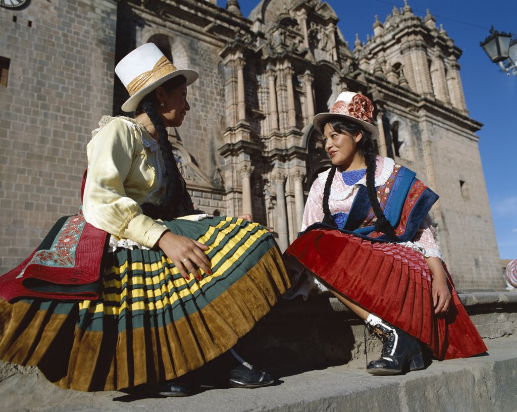 Stock Photo: 442-7773 Two mid adult women dressed in traditional costumes sitting in front of a church, Cuzco, Peru