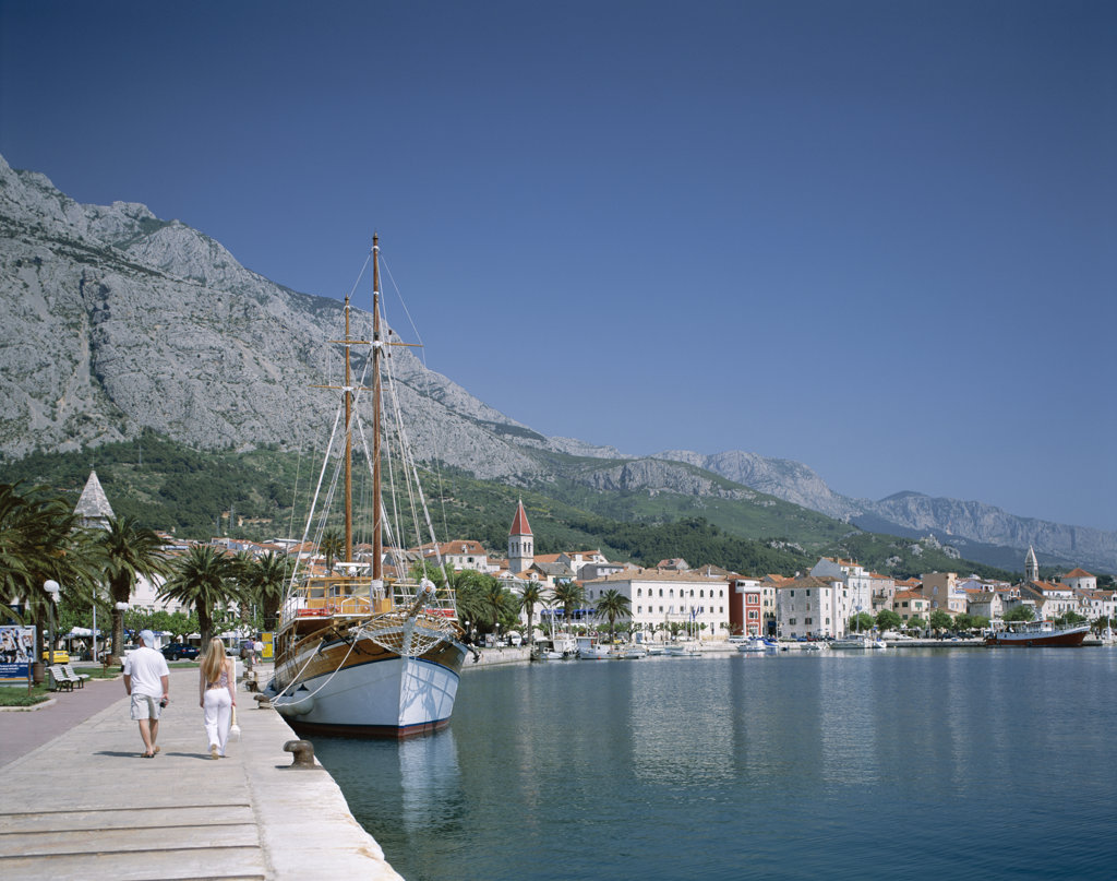 Two people walking at the harbor, Makarska, Dalmatian Coast, Croatia : Stock Photo