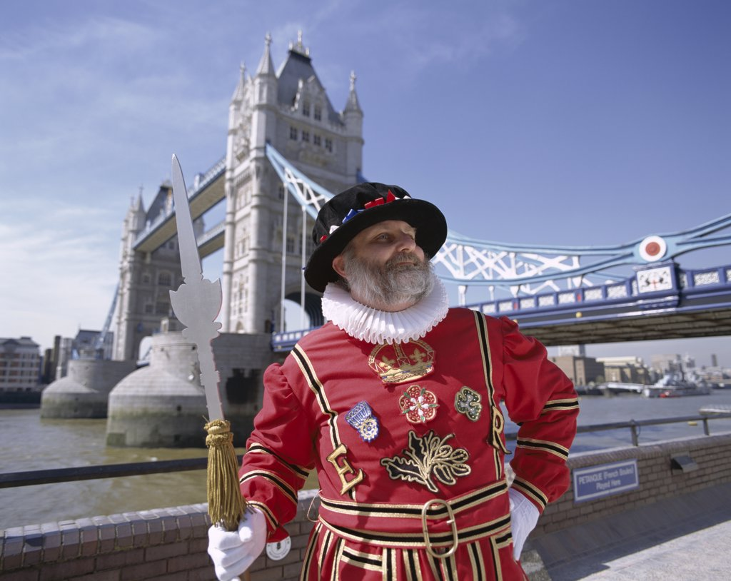 Stock Photo: 442-9494 Beefeater standing in front of the Tower Bridge, London, England