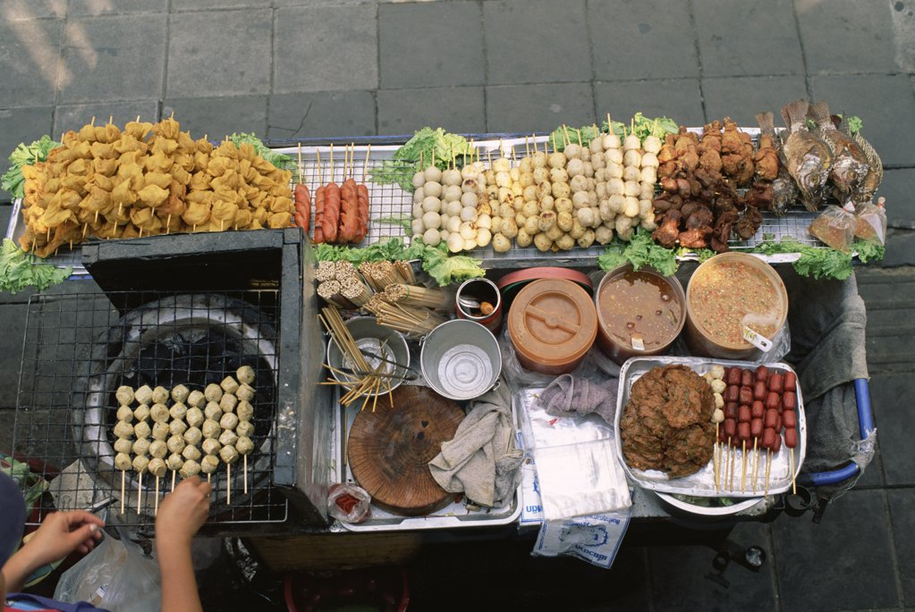 Stock Photo: 442-9736 High angle view of a person's hand cooking kebabs on a street stall, Bangkok, Thailand