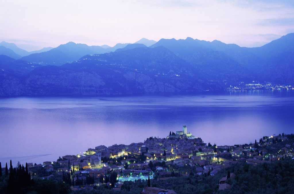 Aerial view of buildings lit up at dusk, Lake Garda, Malcesine, Italy : Stock Photo