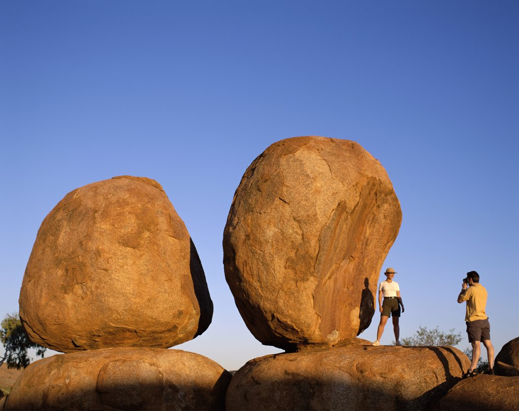 Stock Photo: 442-W9679 Tourist taking photographs of boulders, Devils Marbles, Northern Territory, Australia