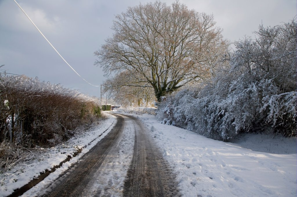 Snow covered lane, with wheel tracks and ice covered telegraph wires, Bentley, Suffolk, England, december 2009 : Stock Photo