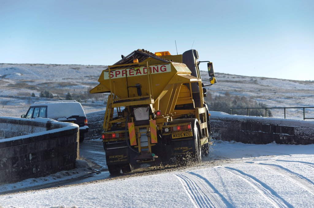 Stock Photo: 4421-32649 Council gritter lorry gritting snow covered rural road, Whitewell, Lancashire, England, november