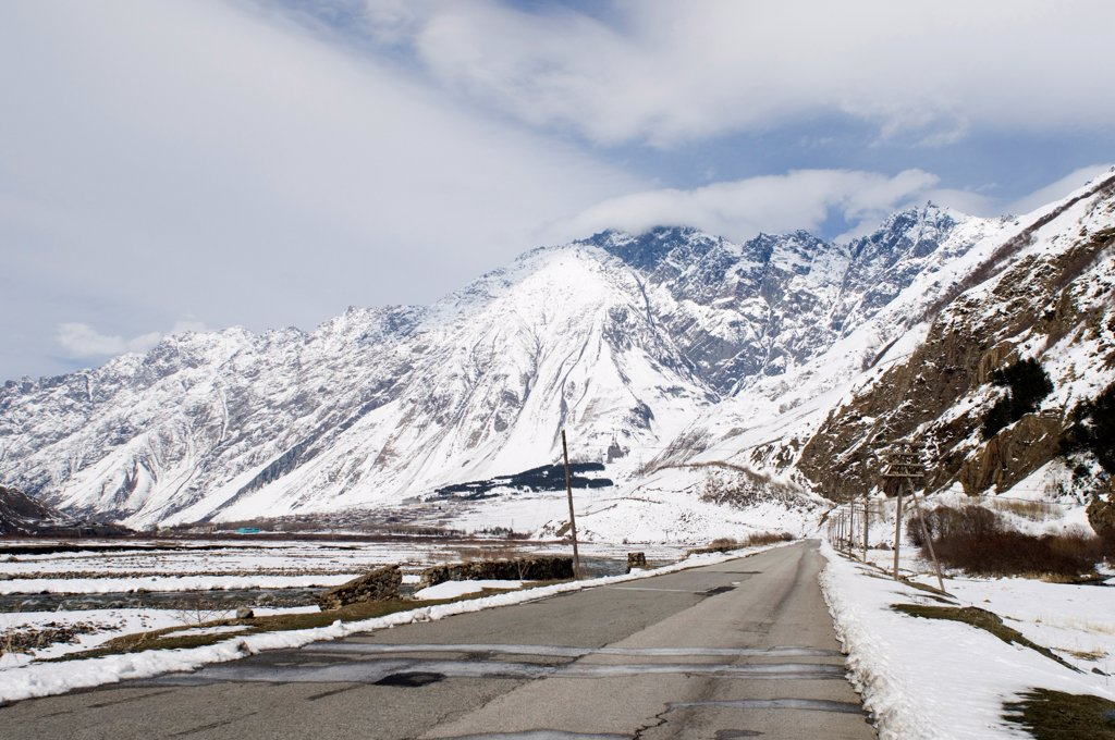 View of road and snow covered mountains, leading to Kazbegi, Great Caucasus, Caucasus Mountains, Georgia, april : Stock Photo