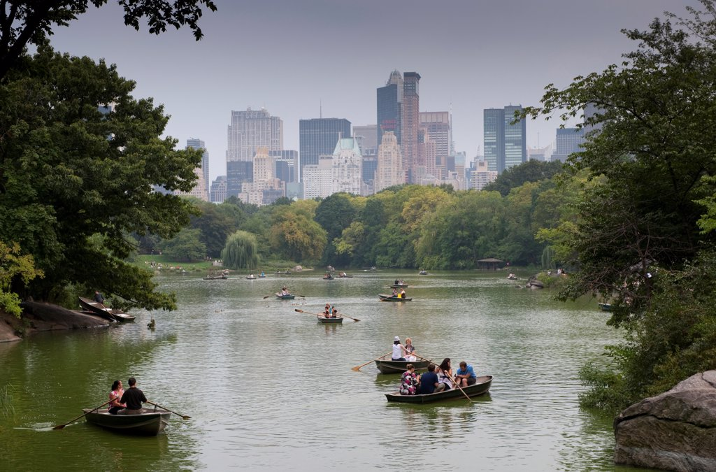 Stock Photo: 4421-33189 Tourists in rowing boats on boating lake in city parkland, with skyline of skyscrapers in background, Central Park, Manhattan Island, New York City, New York State, U.S.A., september