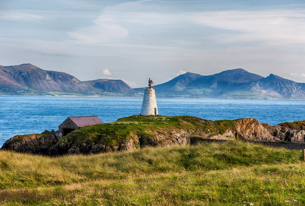 View of lighthouse and coastline on tidal island, Llanddwyn Island, Newborough Warren National Nature Reserve, Newborough, Anglesey, Wales, August : Stock Photo