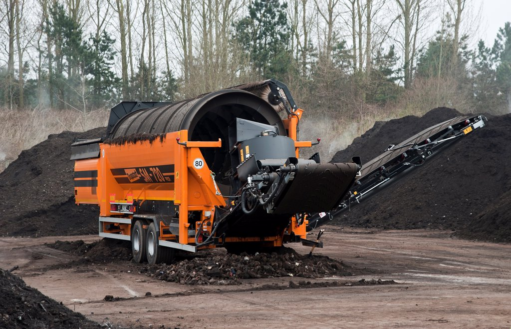 Doppstadt portable trommel screen, used to filter rubbish from green compost at municipal waste site, near Chester, Cheshire, England, march : Stock Photo