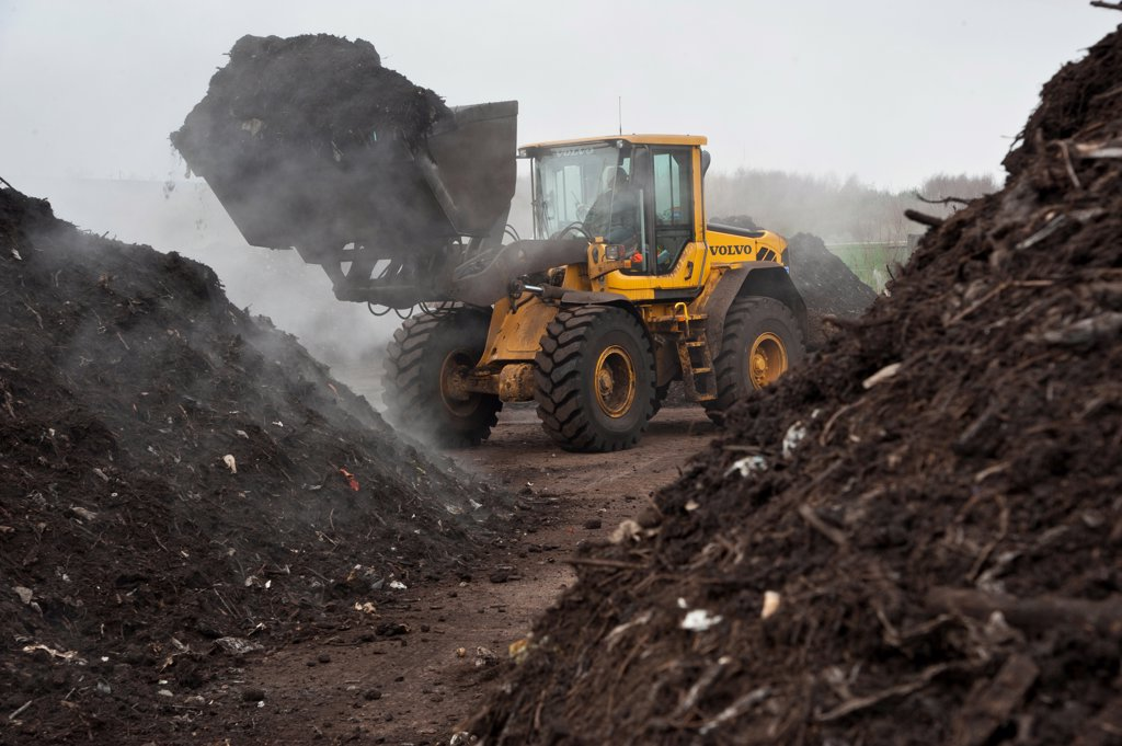 Volvo loader turning green compost waste for aeration at municipal waste site, near Chester, Cheshire, England, march : Stock Photo