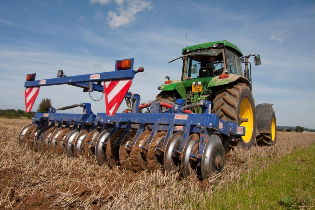 Stock Photo: 4421-40113 Tractor with disc harrows, harrowing stubble field, Sussex, England, september