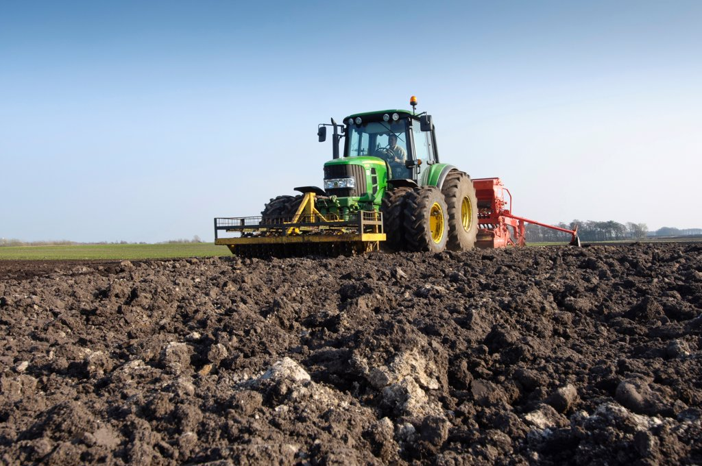 Stock Photo: 4421-40415 Tractor with seed drill, drilling Westminster spring barley, Pilling, Lancashire, England, march