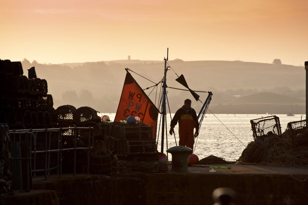 Stock Photo: 4421-40560 Fisherman preparing to go to sea at dusk, in harbour of seaside town, Padstow, Cornwall, England, april
