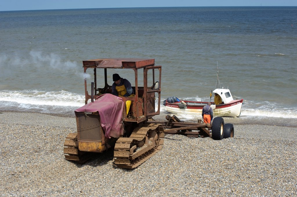 Stock Photo: 4421-40564 Tractor landing fishing boat on beach, Weybourne, Norfolk, England, may