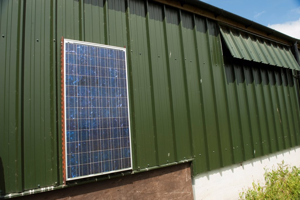 Stock Photo: 4421-41179 Solar energy panels, powering free-range hen unit building, Cumbria, England, june