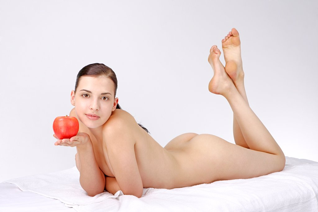 Stock Photo: 4422R-12758 Studio shot of beautiful young woman and apple