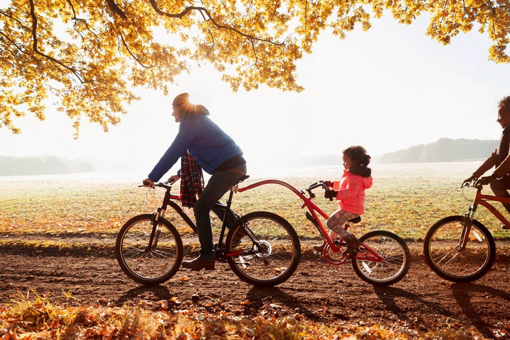 Stock Photo: 4428R-13718576 Father and daughter bike riding with trailer bike in sunny autumn park