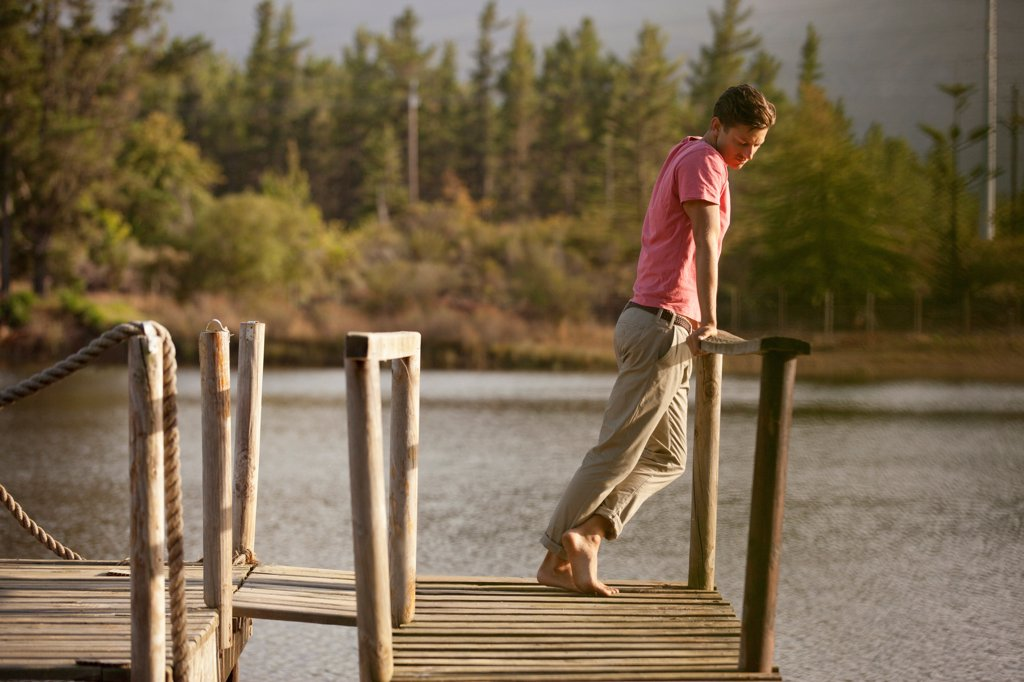 Stock Photo: 4428R-1429 Cape Town, Serene man standing at railing of dock over lake