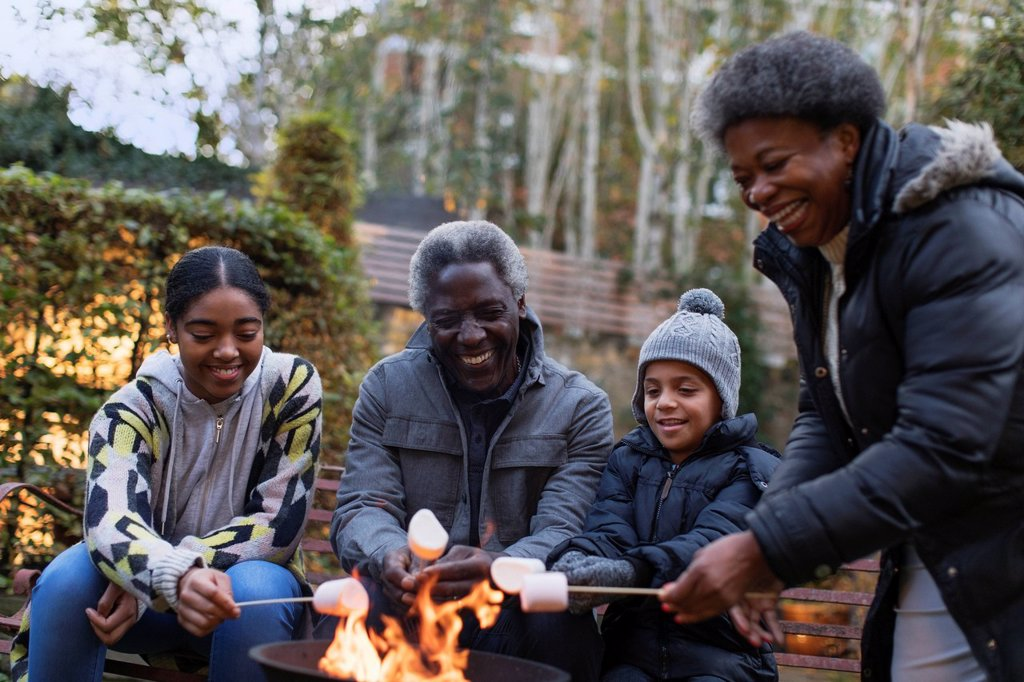 Stock Photo: 4428R-15137795 Grandparents and grandchildren roasting marshmallows over campfire