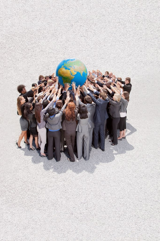 Stock Photo: 4428R-2444 Cape Town, South Africa, Crowd of business people in huddle lifting globe overhead