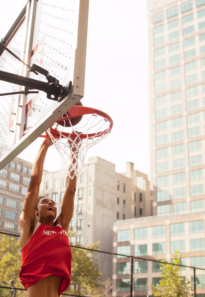Man dunking basketball on court,New York : Stock Photo