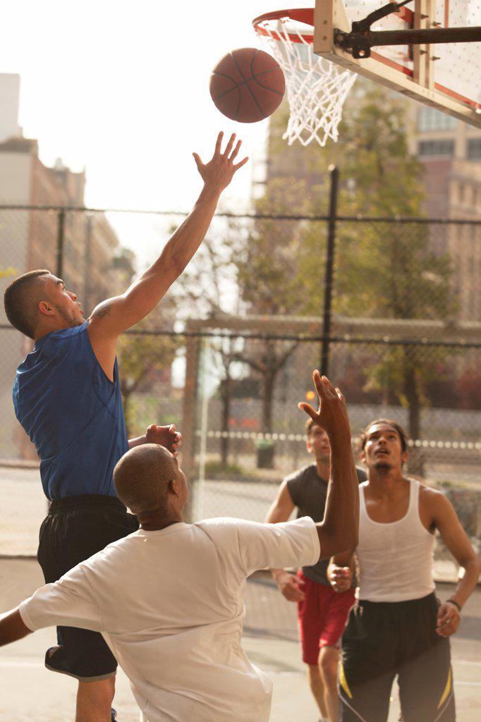 Men playing basketball on court,New York : Stock Photo
