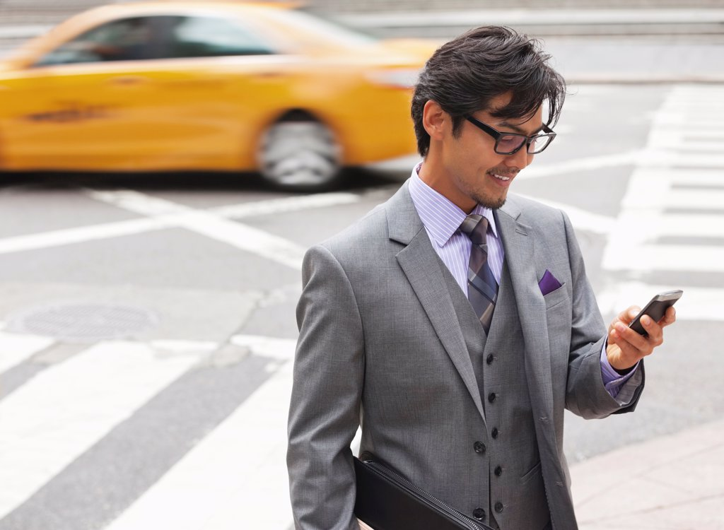 Businessman using cell phone on city street,New York : Stock Photo