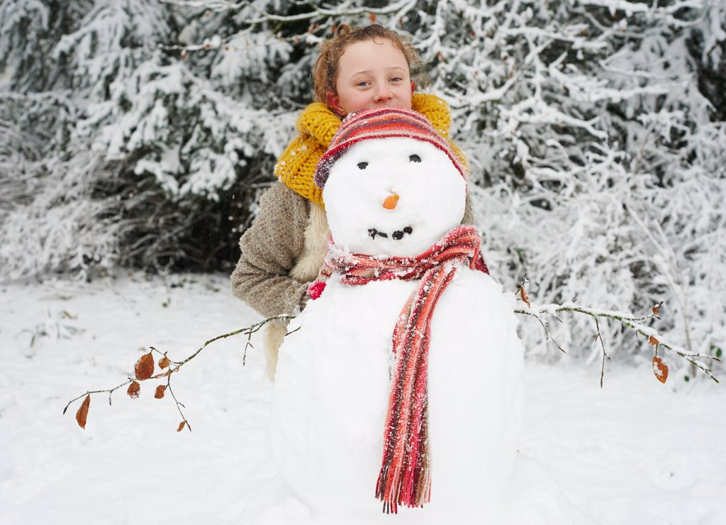 Stock Photo: 4428R-5089 Girl making snowman outdoors