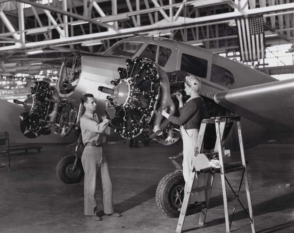 Mid adult man and a mid adult woman examining an airplane, 1943 : Stock Photo