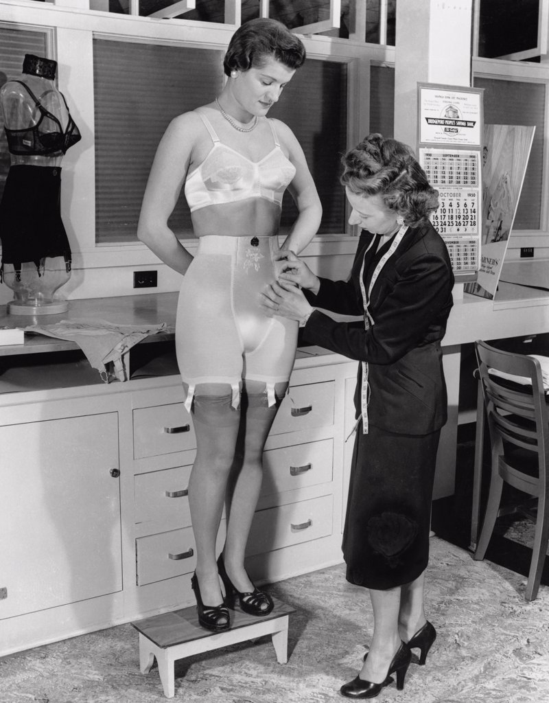 Side profile of a tailor adjusting the seams of a young woman's undergarments, 1950 : Stock Photo