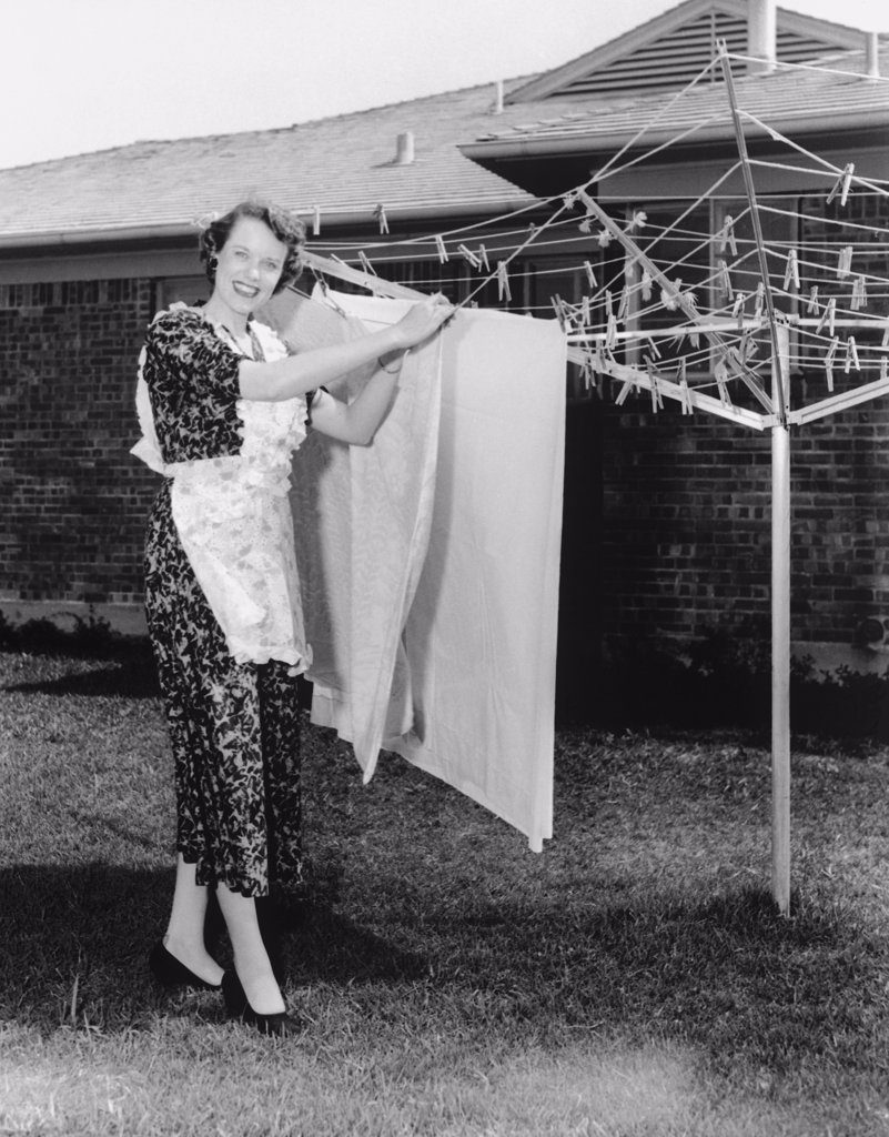 Stock Photo: 443-172 Portrait of a young woman drying clothes on a clothesline, 1950