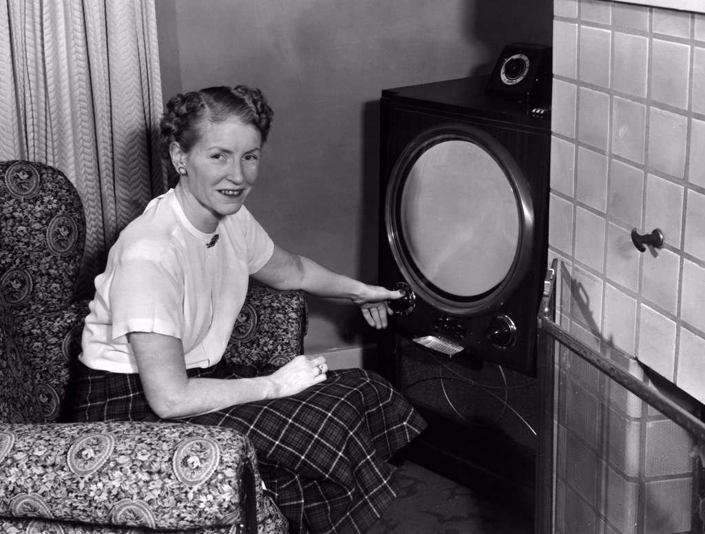 Stock Photo: 443-181 Portrait of a mid adult woman sitting in an armchair in front of a television, 1950