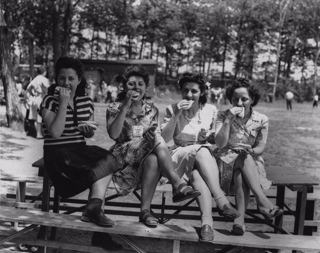 Portrait of four young women eating hot dogs, 1945 : Stock Photo