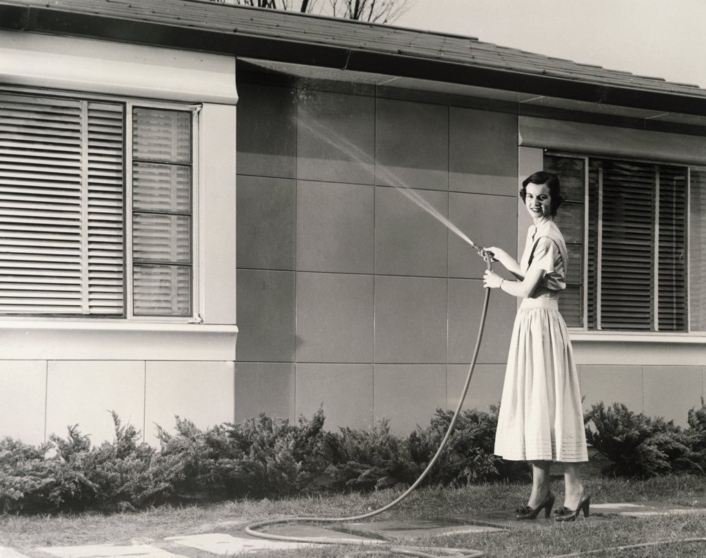 Stock Photo: 443-285 Portrait of a young woman spraying water on the wall of a house