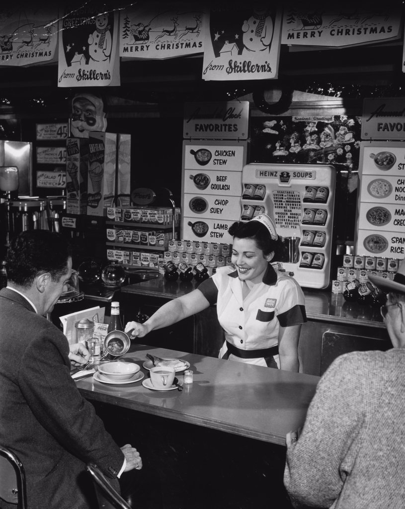 Waitress serving customers in a restaurant, 1953 : Stock Photo
