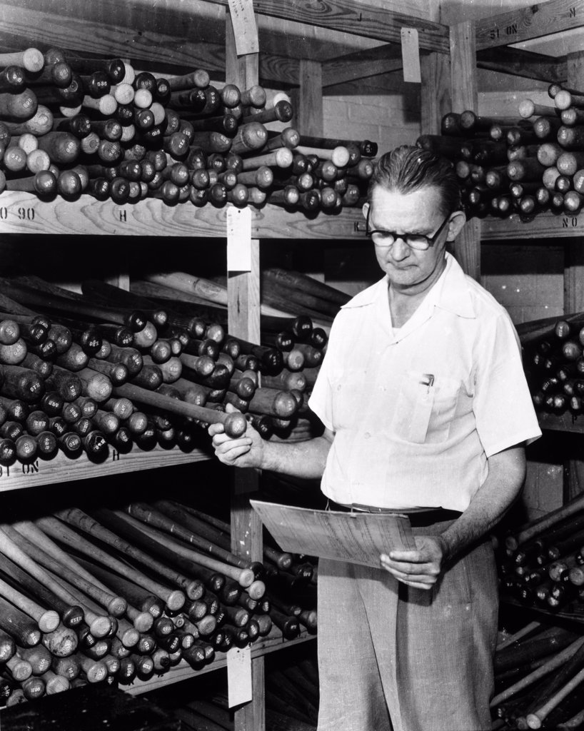 Senior man inspecting a baseball bat in a warehouse : Stock Photo