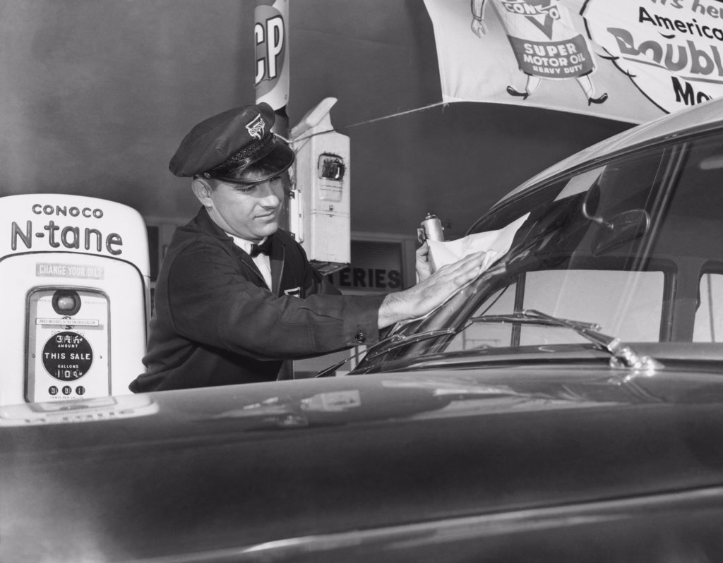 Gas station attendant cleaning a car, 1954 : Stock Photo