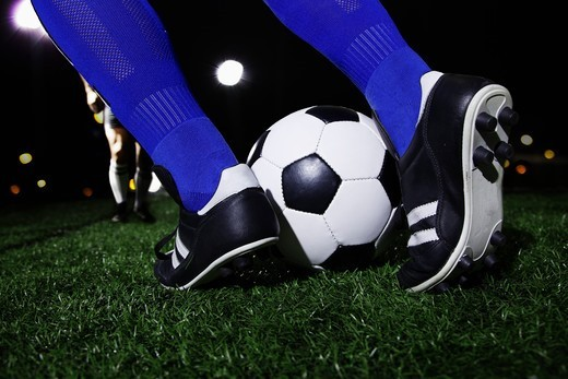 Close up of feet kicking the soccer ball, night time in the stadium : Stock Photo
