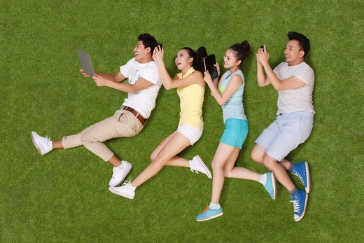 Young people lying on grass looking at phone and tablet : Stock Photo