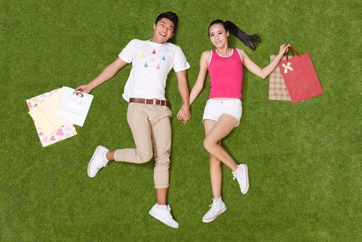 Stock Photo: 4445R-10887 Young couple holding shopping bags lying on grass