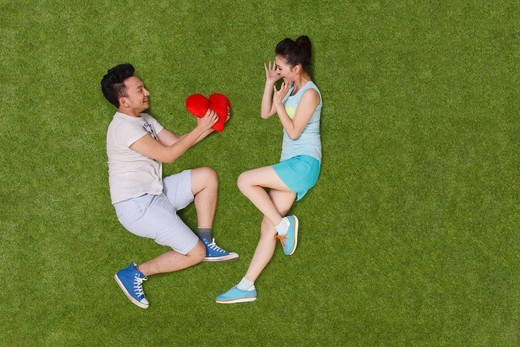 Stock Photo: 4445R-10891 Young couple lying on grass