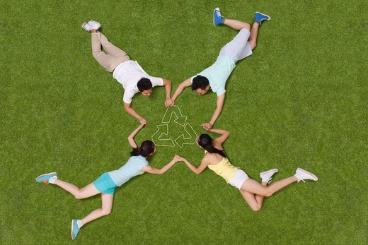 Young people lying on grass hand in hand : Stock Photo