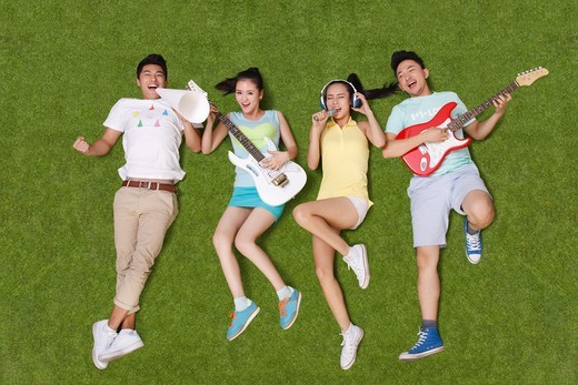 Young people on grass playing musical instruments : Stock Photo