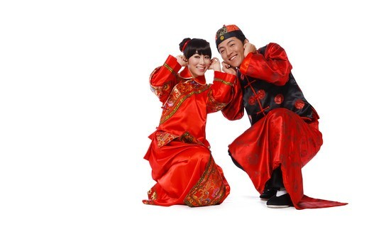 Stock Photo: 4445R-11643 Young couple in traditional clothes with fire cracker